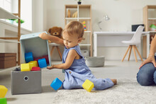 Cute Little 2 Year Old Child Putting Toys Back In Their Place, Helping Mommy To Tidy Up
