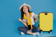 Asian Woman Tourist In Casual Clothes Sit Near Suitcase Isolated On Blue Background. She Showed Joy That Clenched Both Hands.