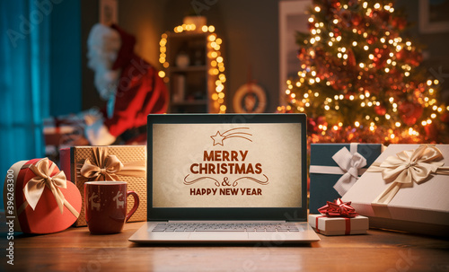 Obraz Christmas wishes on a laptop and Santa bringing gifts at home - fototapety do salonu