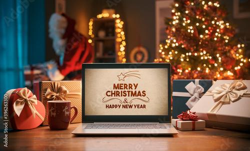 Fototapeta Christmas wishes on a laptop and Santa bringing gifts at home obraz