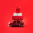 Leinwandbild Motiv Red toy car with Christmas presents on red isolated background.