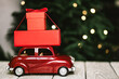Leinwandbild Motiv Red toy car with Christmas presents with festive lights on background.
