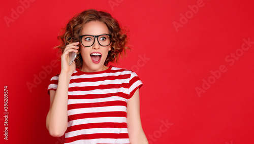 Surprised woman speaking on smartphone.