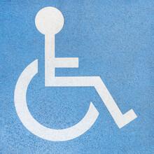 Rollstuhlfahrer - Weißes Zeichen Auf Einer Blauen Betonplatte - Markierung Am Boden Für Einen Behindertenparkplatz