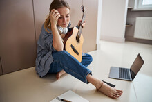 Charming Young Woman With Guitar Writing Songs At Home