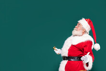 Surprised Santa Claus With A Gold Bell On A Green Studio Background.
