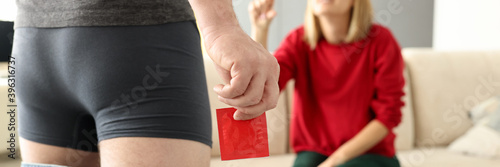 Foto Man in shorts pulling jeans down stands with condom in hand close-up in front of girl