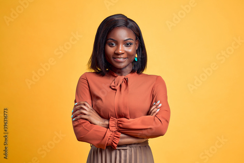 Advertising concept. Confident and smiling young african american woman crossed hands on chest, looking at camera and standing on yellow copy space background. - fototapety na wymiar