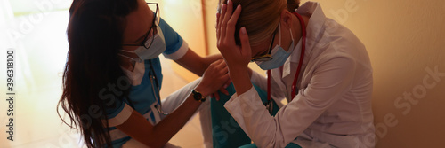 Nurse calms crying doctor wearing medical protective mask in bright hospital corridor Canvas