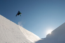 Snowboarder Performing Stunts On A Sunny Day At Park