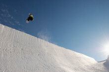 Snowboarder Performing Stunts In Park Against Blue Sky