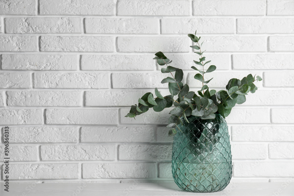 Fototapeta Beautiful eucalyptus branches in glass vase on white wooden table near brick wall. Space for text