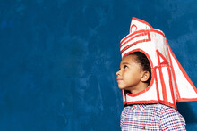 Afro-american Kid Boy With Craft Rocket On Head. Close Up Side View Of Cute Little Child With Spaceship, Portrait With Copyspace For Advertising Text. Space Learning And Education Concept.