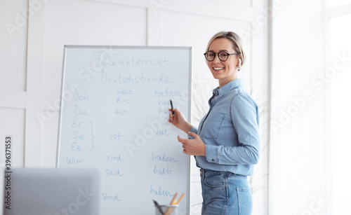 Obraz Happy young teacher standing near blackboard and explaining German lesson to students online from home, panorama - fototapety do salonu