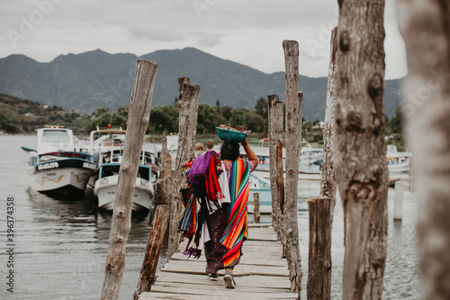 Cuadros en Lienzo Traditional Mayan Woman in colorful clothing selling scarves on the docks of Lak