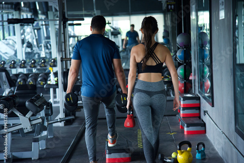 Man and woman in a gym where they are moving and arranging the accessories they Canvas Print