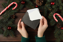 Woman Taking Blank Christmas Card From Envelope At Wooden Table, Top View With Space For Text