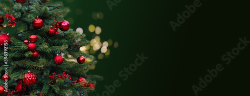 Closeup of Festively Decorated Outdoor Christmas tree with bright red balls on blurred sparkling fairy background. Defocused garland lights, Bokeh effect