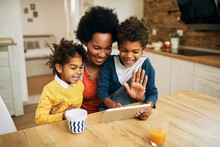 Happy Black Mother And Her Kids Having Video Call Over Touchpad At Home.