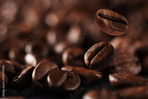 Fototapeta Falling roasted coffee beans background with copy space. Coffee beans in the factory. Coffee beans fall onto the table. obraz na płótnie