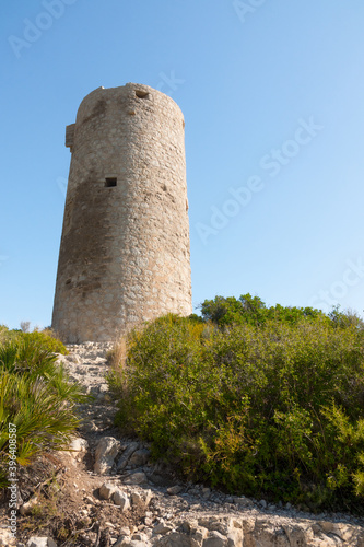 Medieval castle watchtower ruin. Torre Abadum or Badum tower. Beautiful protected Serra d'Irta Natural Park, Peniscola, Castellon province, Spain. Vertical shot.