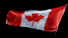 Canadian Flag Blowing In The Wind Isolated Against A Black Background.