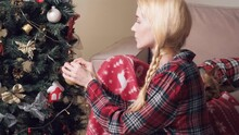 Cute Beautiful Young Blonde Woman Hangs A Golden Christmas Ball On The Christmas Tree. A Small Pomeranian Dog Is Lying On The Sofa.