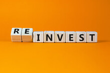 Reinvest Symbol. Inverted Wooden Cubes With Words 'invest - Reinvest'. Beautiful Orange Background. Business And Reinvest Concept. Copy Space.