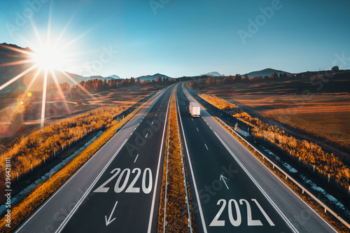 Driving on open road at beautiful sunny day to new year 2021. Aerial view