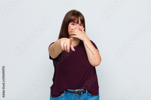 Photo overweight woman laughing at you, pointing to camera and making fun of or mockin