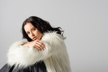 Young Woman In Faux Fur Jacket Posing On White Background