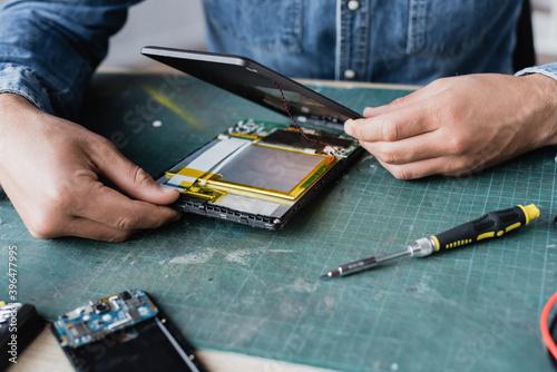 Close up view of repairman hands disassembling broken digital tablet near screwd Fototapet
