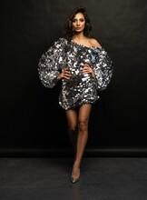 Beautiful Sexy Woman Wearing Sparkle Dress On Black Background.