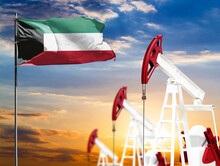 Oil Rigs Against The Backdrop Of The Colorful Sky And A Flagpole With The Flag Of Kuwait. The Concept Of Oil Production, Minerals, Development Of New Deposits.