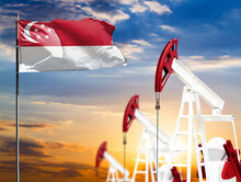 Oil Rigs Against The Backdrop Of The Colorful Sky And A Flagpole With The Flag Of Singapore. The Concept Of Oil Production, Minerals, Development Of New Deposits.