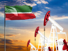 Oil Rigs Against The Backdrop Of The Colorful Sky And A Flagpole With The Flag Of Tatarstan. The Concept Of Oil Production, Minerals, Development Of New Deposits.