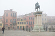 Ancient beautiful square with an equestrian statue and buildings in Venice, Italy, foggy weather. Splendid medieval architecture, detail.