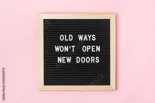 Old Ways Won't Open New Doors. Motivational quote on black letter board on pink background. Concept inspirational quote of the day. Greeting card, postcard
