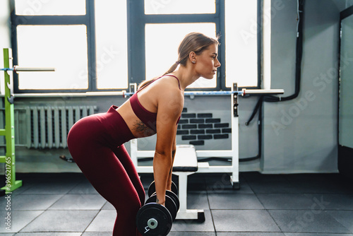 Fotografiet Focused sportswoman doing exercise with dumbbells while working out