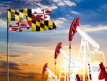 Oil Rigs Against The Backdrop Of The Colorful Sky And A Flagpole With The Flag State Of Maryland. The Concept Of Oil Production, Minerals, Development Of New Deposits.