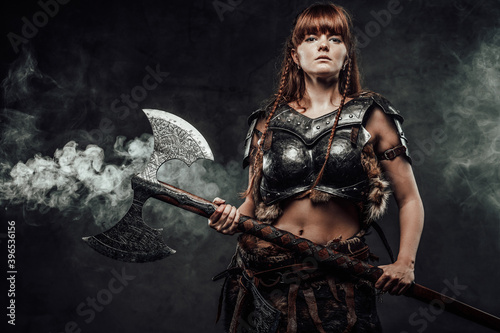 Canvas Print Portrait of warlike female fighter from north with long brown hairs in dark armour with two handed axe in dark smokey background
