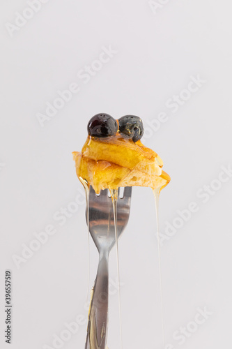 Close up of pancake and berries with dripping honey on fork on white background