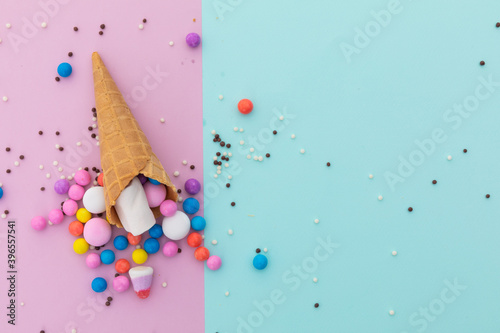Ice cream cone and scattered colourful sprinkle on pink and blue background