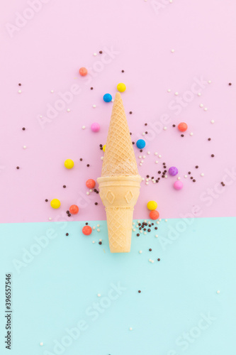 Two ice cream cones and scattered colourful sprinkle on pink and blue background
