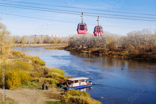 Fényképezés Ural river, Orenburg, Russia - October, 18, 2020: Cable car and pleasure boat ne