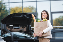 Woman Looking At Camera While Standing Near Open Car Trunk While Holding Shopping Bag