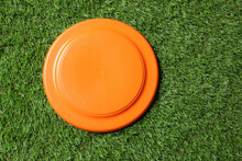 Orange Plastic Frisbee Disk On Green Grass, Top View