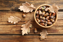 Acorns And Oak Leaves On Wooden Table, Flat Lay
