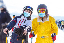 Group Of Happy Friends Having Fun. Young People With Face Mask During COVID-19 Coronavirus On A Snowy Mountain At A Ski Resort