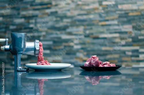 Grinding fresh red meat on a metal manual meat grinder, close-up on a brick wall Fototapet